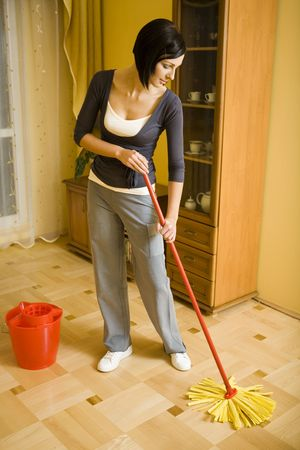 Young woman with the mop wipes the floor in room. Whole body. Front view.