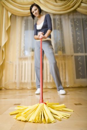 focused: Woman standing in room with mop. Focused on mop. Looking at camera.Whole body.  Low angle view.