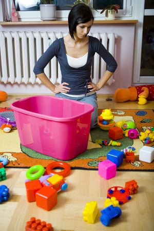 Young woman kneeling at container with toys and assembles strewn toys. She looks like thought about something. Front view. photo