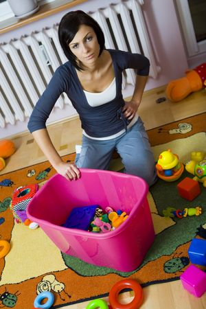 woman kneeling: Young woman kneeling at container with toys and assembles strewn toys. High angle view. Stock Photo
