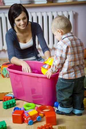 messy room: Young woman with  boy during playing. Woman showing toy to . They are at container with toys.  standing back to camera. Front view.