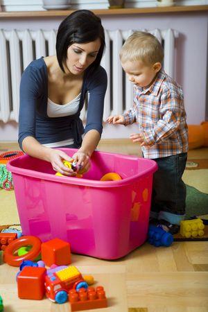 disordine: Giovane donna con bambino ragazzo durante plaing. Donna mostrando giocattolo per bambini. Essi sono al contenitore con i giocattoli. Vista frontale.