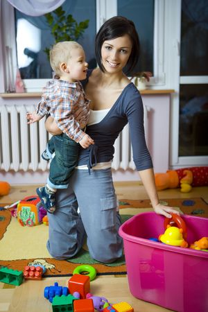 Young woman with  boy during plaing. Woman holding  on hand taking toy from container. Front view. photo
