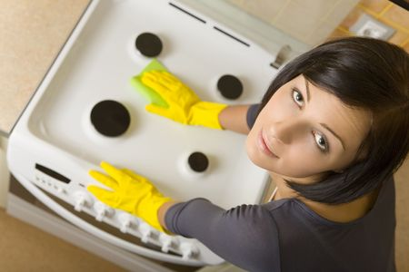 washcloth: Young woman in yellow rubber gloves cleaning cooker. Looking at camera. High angle view.