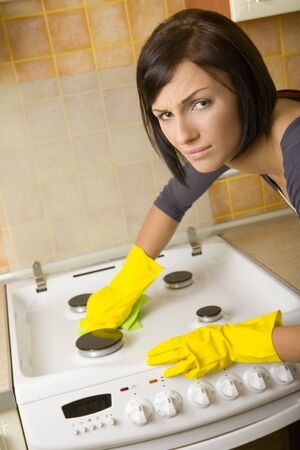 Young woman in yellow rubber gloves cleaning cooker. Looking at camera. Front view. Stock Photo