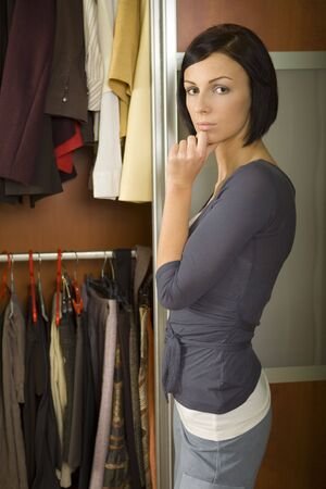 Young woman standing at wardrobe. She thinking of what to wear. Looking at camera. photo