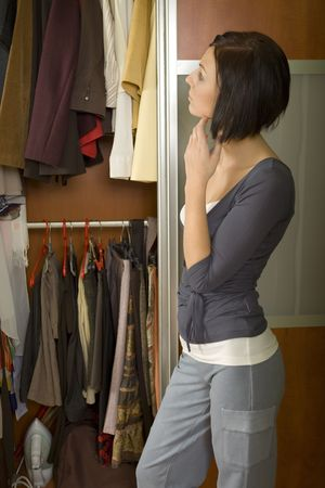 get dressed: Young woman standing at wardrobe. She thinking what get dressed.  Stock Photo