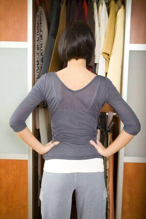 Joven mujer de pie delante del armario. Ella pensando qué vestirse. Ella de pie de nuevo a la cámara.