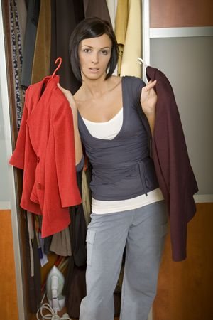 Young woman standing at wardrobe and chooses what can to dress. looking at camera. Front view.