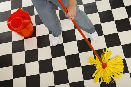 Woman standing with mop beside red bucket. Closeup on womans legs and mop High angle view. White background. Stock Photo