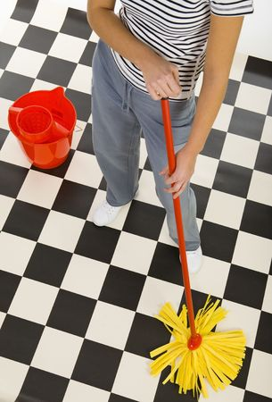 Woman standing with mop beside red bucket. View on down parts womans body. High angle view. White background.