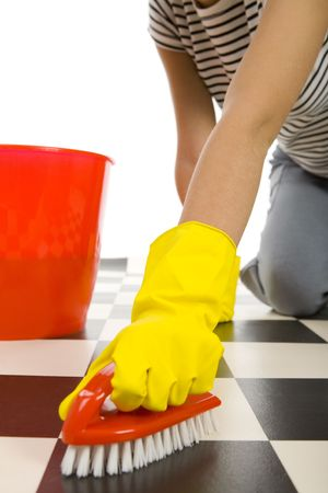 brush in: Young woman in yellow rubber gloves kneeling and scrubs the floor. Closeup on hand in glove with brush.