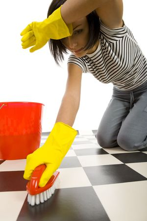 Young woman in yellow rubber gloves kneeling and scrubs the floor. Shes looks like tired. Front view. White background.