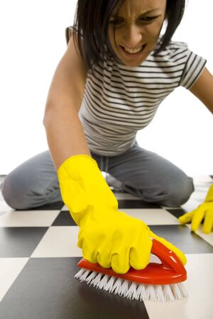 houseclean: Young woman in yellow rubber gloves kneeling and scrubs the floor. Focused on hand in glove with brush. Front view. White background. Stock Photo