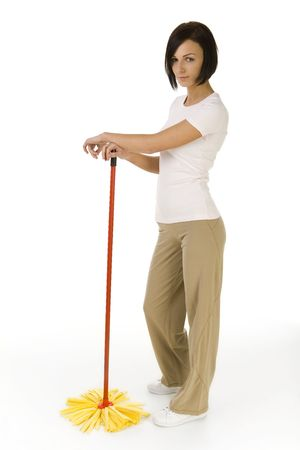 houseclean: Young woman standing with mop and looking at camera. Whole body. Side view. White background.