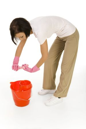 washcloth: Young bent woman wringing washcloth to red bucket. Side view, white background.