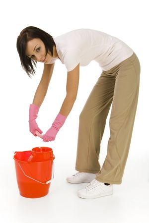 washcloth: Young bent woman wringing washcloth to red bucket. Looking at camera, side view. White background.