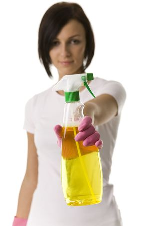 Young woman standing and holding in hand bottle of cleanser. Looking at camera, front view. Focused on hand with bottle. White background. Stock Photo - 2651543