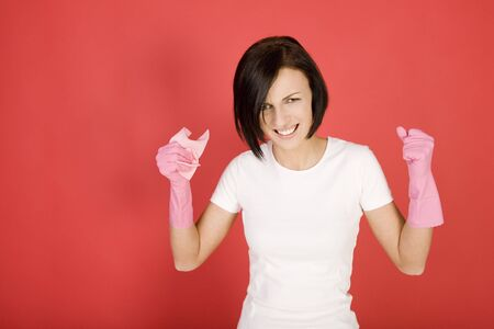 Young woman in pink rubber gloves holding in hand washcloth. She has clenched fists. Shes looks like very angry.  Looking at camera, front view. photo