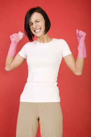 express feelings: Young screaming woman in pink rubber gloves holding in hand washcloth. She has clenched fists. Shes looks like very angry. Front view.