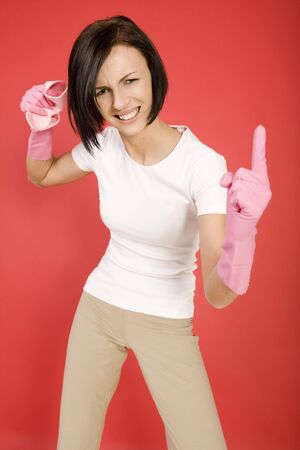 Young woman in pink rubber gloves holding in hand washcloth and threateningly finger. Shes looks like very angry. Looking at camera, front view. photo