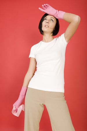 washcloth: Young woman in pink rubber gloves holding in hand washcloth. Shes looks like exhausted. Front view.