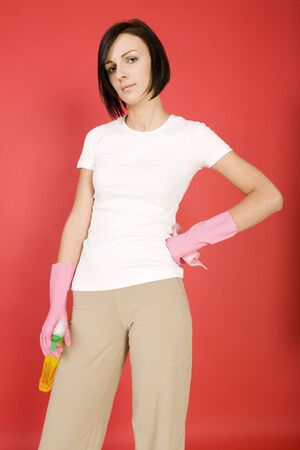express feelings: Young woman in pink rubber gloves holding in hands washcloth and bottle of cleanser. Looking at camera, front view.