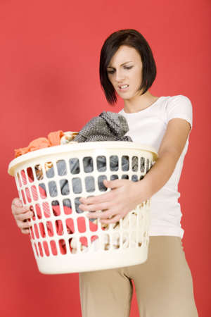 express feelings: Young woman standing with full laundry basket. Shes looks like angry. Front view. Stock Photo