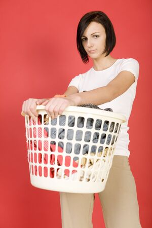 express feelings: Young woman standing with full laundry basket. Looking at camera. Front view. Stock Photo