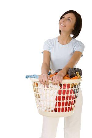 casalinga: Giovane donna in piedi felice con cesto pieno di lavanderia. She's somiglia MOONY. Vista frontale, bianca, backgroun.
