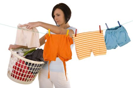 grime: Young woman hanging clothes on clothesline using clothespin. She holding clothes hamper in hands. Front view, looking at camera. White background.
