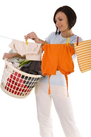 grime: Young smiling woman hanging clothes on clothesline using clothespin. She holding clothes hamper in hands. Front view, looking at camera. White background.