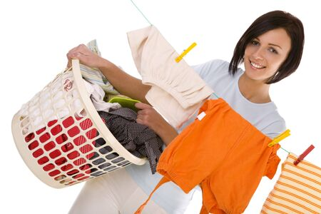 hanging clothes: Young smiling woman hanging clothes on clothesline using clothespin. She holding clothes hamper in hands. Front view, looking at camera. White background.