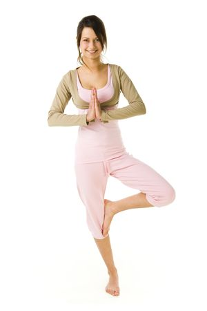 sportingly: Young woman standing on one leg during exercises of yoga. Looking at camera and smiling. Whole body. Front view. White background.