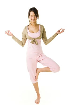 Young woman standing on one leg during exercises of yoga. Looking at camera and smiling. Whole body. Front view. White background. Stock Photo - 2852423