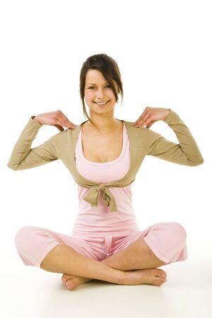Young woman sitting cross-legged during exercises of yoga. Looking at camera and smiling. Whole body. Front view. White background. Stock Photo - 2852430