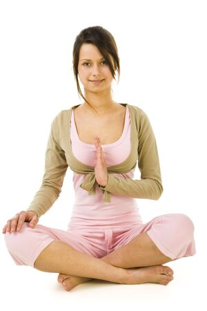 sportingly: Young woman sitting cross-legged during exercises of yoga. Looking at camera and smiling. Whole body. Front view. White background.