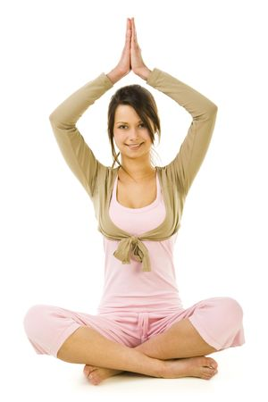 sportingly: Young woman sitting cross-legged with hands over head during exercises of yoga. Looking at camera and smiling. Whole body. Front view. White background.