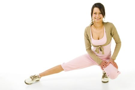 sportingly: Young woman in pink sportswear during streaching. Looking at camera and smiling. Whole body. Front view. White background.