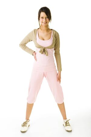 Young woman in pink sportswear during exercising. Looking at camera and smiling. Whole body. Front view. White background. Stock Photo - 2852422
