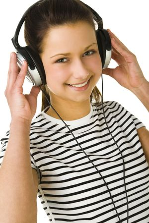 Young woman listening to music by headset. Looking at camera and smiling. Front view. White background. photo