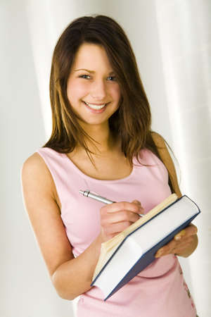 succesful woman: Beautiful student in pink shirt holding books and takes notes. Looking at camera and smiling. Front view.