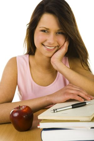 succesful woman: Young happy woman sitting at desk. Looking at camera. On the desk lying books and red apple. Front view. White background.