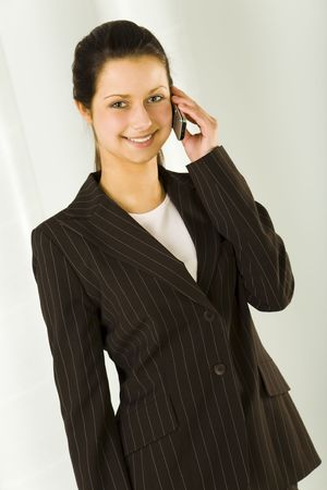 Young bussineswoman talking by mobile phone. Looking at camera and smiling. Front view. photo