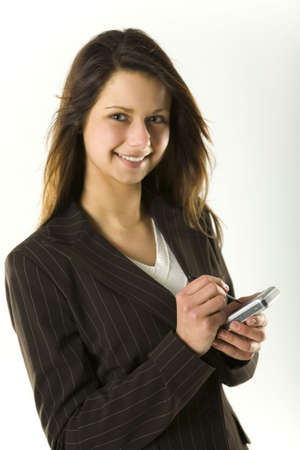 Young bussineswoman using palmtop to sending message. Looking at camera and smiling. photo