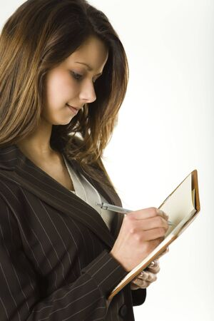 Young woman holding notepad and takes notes. Side view photo