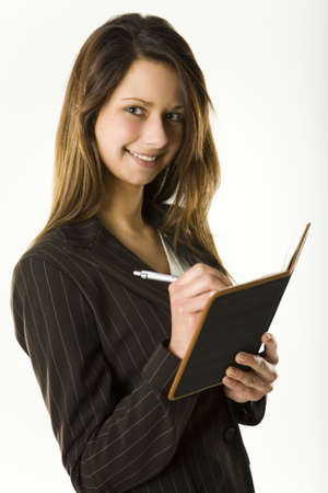Young woman takes notes in notepad. Looking at camera and smiling. photo