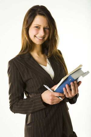 Young woman holding books and takes notes. Looking at camera and smiling. Front view.  photo