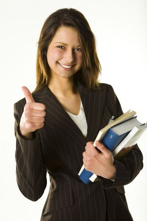 Young woman holding books and showing OK. Looking at camera and smiling. Front view. photo