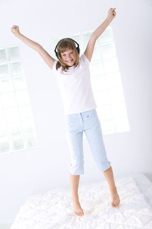 Young happy girl with earphones jumping on a bed. She's hands up with clenched fist. She's looking at camera. Stock Photo - 3597654